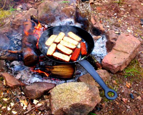 brutzelnde Pfanne auf Lagerfeuer