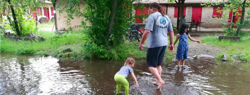 Daniel und zwei Kinder in einem aus Regenwasser entstandenen Planschbecken