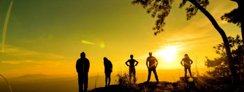 Jugendliche, die sich den Sonnenuntergang anschauen.
