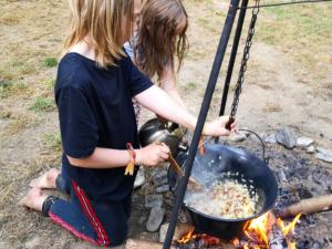 zwei Kinder kochen am Feuer