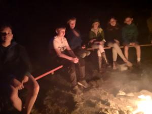 Kinder sitzen am Feuer