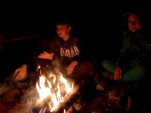 Kinder sitzen am Feuer III