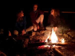 Kinder sitzen am Feuer II