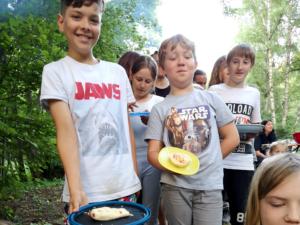 Kinder stehen Schlange mit ihren Pizzen